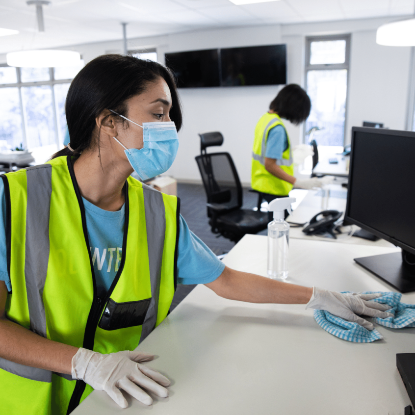 visual image of commercial cleaner wiping down desk and keyboard